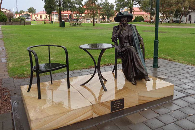 Bronzed statue of the late mayor of Port Augusta, N. Joy Baluch AM, seated at a cafe style table with an empty seat beside her