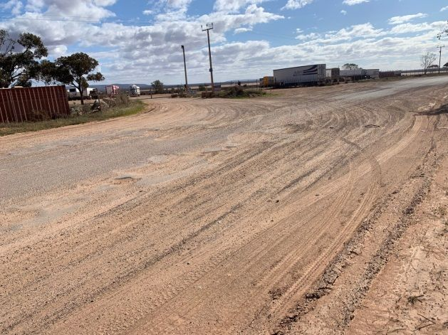 Photograph of Old Tarcoola Road showing potholes and degradation/erosion of bitumin surface, exposing the gravel beneath