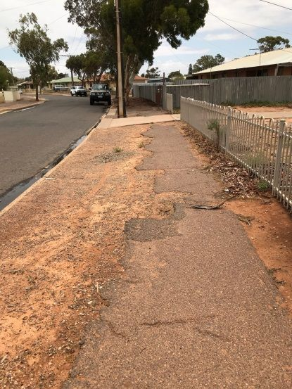 Photograph of bitumin footpath on Mealy Street showing edge erosion, potholes, missing sections and cracks