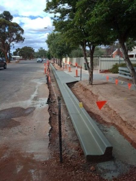 Concrete kerbing under construction along Stokes Terrace. The road and footpath have been excavated either side of where the wet concrete is sitting, drying, surrounded by orange hazard flags.